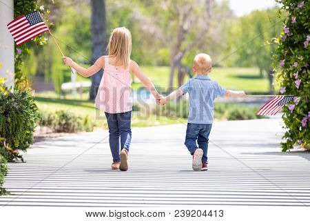 Young Sister and Brother Holding Hands and Waving American Flags At The Park.