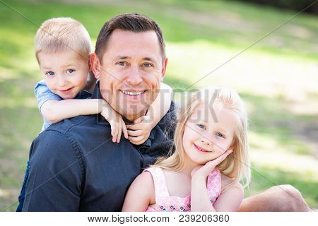 Young Caucasian Dad, Son and Daughter Having Fun In The Park.