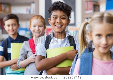 Portrait of a happy multiethnic children holding books and wearing backpack at primary school. Schoolboys and cute girls in a row holding notebook and looking at camera. Elementary child smiling.
