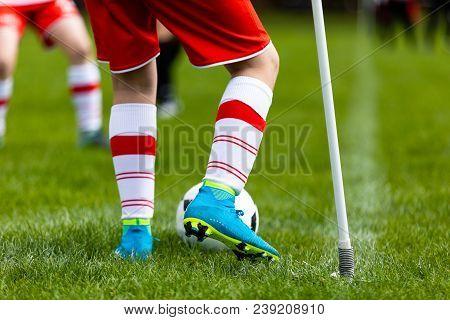 Young Football Player Kicking Ball On Soccer Field. Soccer Player Kicking Ball On Corner Of Soccer P