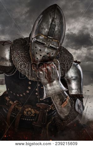 Thoughtful Knight Over Dark Clouds Background. Knight With Sword In Battlefield.