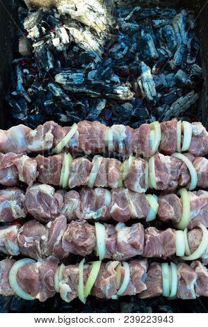 Skewers With Meat And Onions On The Grill, In Which Black And Gray Coals Are Smoldering