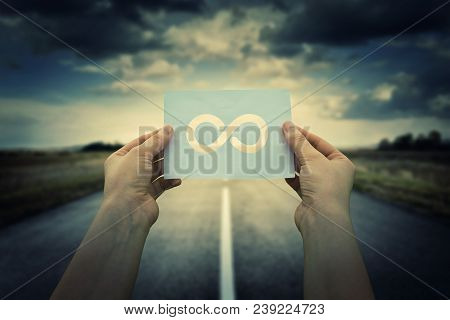 Close up of woman hands holding a paper sheet with infinite sign inside, over endless asphalt road background. The infinity way to nowhere, business confusion concept. poster