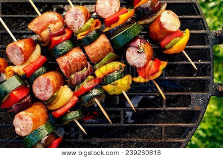 Grilled Skewers Of Meat, Sausages And Various Vegetables On A Grill Plate, Outdoors, Top View. Grill