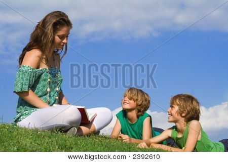 Happy Family Reading Outdoors