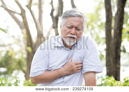 Senior Asian Man Suffering From Chest Pain At Outdoor Place. Old Man Holding Chest With Painful Feel