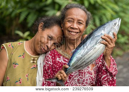 BANDA NEIRA, MALUKU ISLANDS, INDONESIA, DECEMBER 16, 2017 : Cheerful Woman showing fresh Skipjack fish in Banda Neira, Maluku islands, Indonesia.