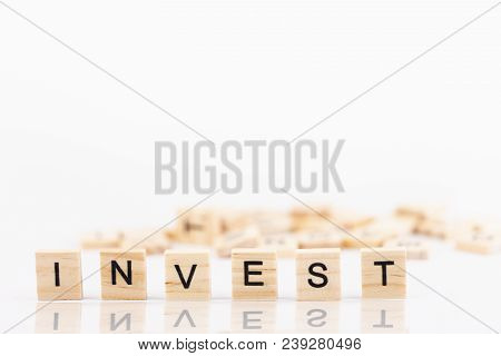 Business Investment Concept. Wooden Cube With Word Invest On White Background. With Copy Space. Succ