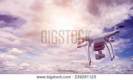 unmanned multicopter drone flying in front of an epic sky with wonderful sun flare