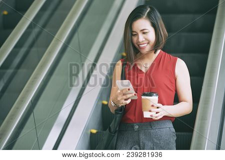Smiling Young Female Entrepreneur Drinking Coffee And Texting With Coworker