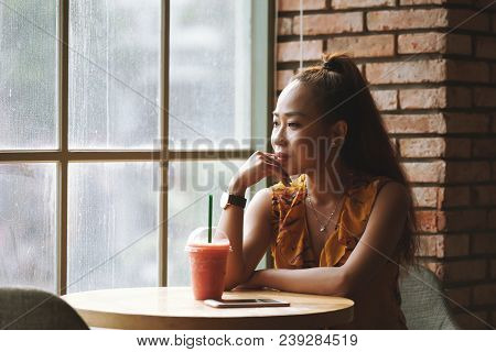 Pensive Young Vietnamese Woman Drinking Smoothie In Cafe