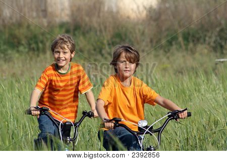 Happy Children Playing On Bicycles