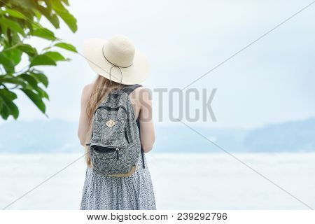 Girl In A Hat With A Backpack Standing On A Pier At The Sea. Mountains On The Background. Back View