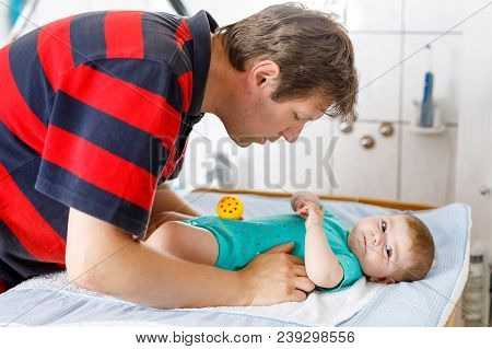 Loving Father Changing Diaper Of His Newborn Baby Daughter. Little Child, Girl On Changing Table In
