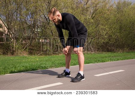Catch Breath! Full Length Picture Of The Young Athlete Runner Deeply Breathing After A Good Jogging