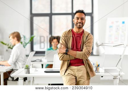 business and people concept - happy smiling indian man with smart watch at office