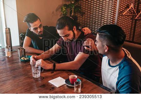Supportive young men encourage their brokenhearted friend. Arabian guys cheer him up and advise in restaurant. Friendship concept. poster