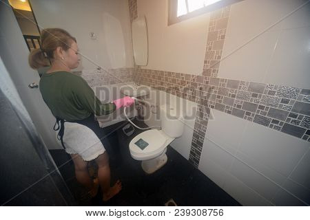 Asian Female Maid Or Housekeeper Cleaning Spray On Water Closet In Toilet.