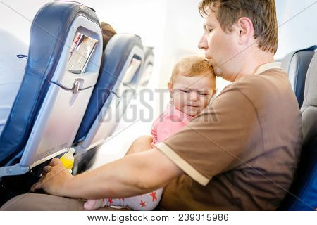 Young Tired Father And His Crying Baby Daughter During Flight On Airplane Going On Vacations. Dad Ho