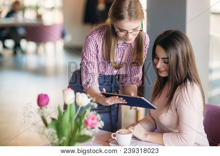 Attractive Young Waitress Using A Tablet Computer To Take An Order From A Customer In A Coffee Shop.