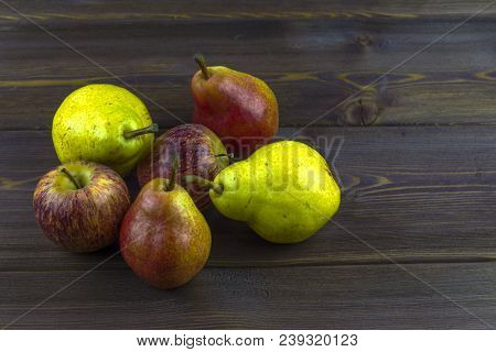 Several Pears And Apples On A Wooden Table