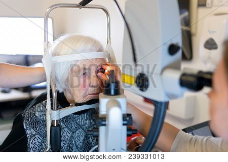 Elderly 95 Years Old Woman During Laser Surgery At Ophthalmology Clinic. Senior Woman Face And Eye W