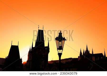 Sunset Backlit Silhouettes Of Street Lamp Post And Roofs Of Cityscape Skyline At Charles Bridge In P