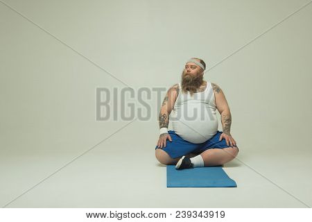 Full Length Portrait Of Serene Thick Man Is Sitting On Mat While Looking Aside Pensively. He Is Rest