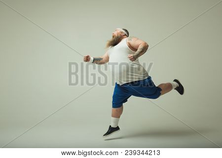 Excited Fat Man Is Running Forward With Aspiration. Copy Space In Left Side