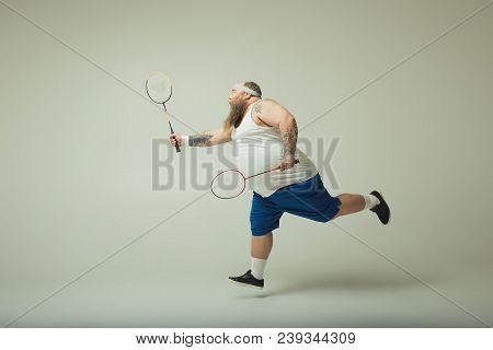 Cheerful Thick Guy Is Playing Tennis With Excitement. He Is Running And Raising Racquet. Copy Space