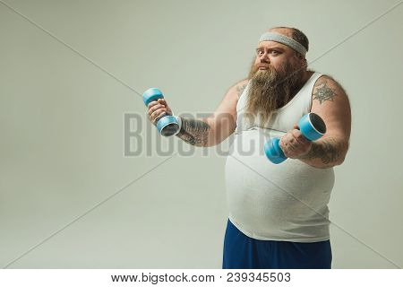 It Is So Heavy. Portrait Of Obese Sportsman Training With Dumbbells. He Is Looking At Camera With Di