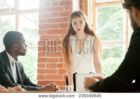 Serious Female Team Leader Explaining Business Problems To Attentive Male Subordinates, Talking Abou