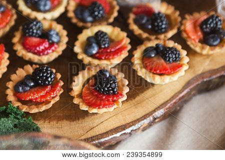 Closeup of berry mini tarts on wooden board. Small tartalettes for party dessert stand. Candy bar and catering concept for birthday, wedding and other holiday celebration poster
