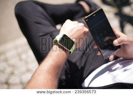 Bucharest, Romania, - October 26, 2017: Person Using Smart Watch And A Smartphone Walking On The Par