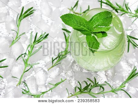 Refreshing Drink With Mint Leaves In Large Wineglass Surrounded By Ice Cubes. Close-up, Top View. Co