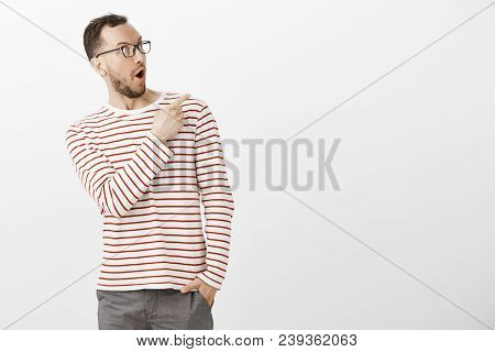 Portrait Of Amazed Pleased Cute Guy In Striped Pullover And Glasses, Saying Wow While Pointing At Up