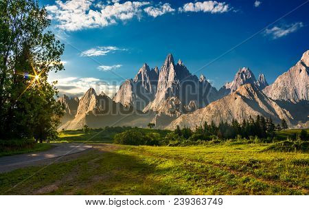Composite Landscape With Rocky Peaks At Sunset. Beautiful Mountainous Scenery With Road Going Throug