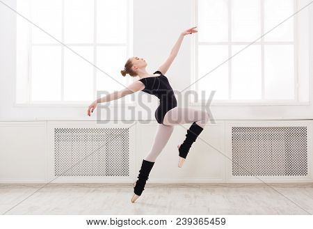 Young Graceful Ballerina In Black At Ballet Class Making Pirouette. Classical Dancer In White Hall P