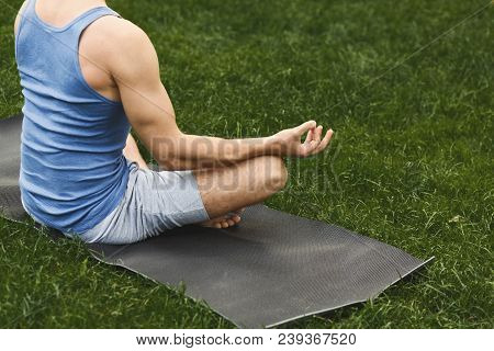 Young Man Practicing Yoga, Meditation Exercises. Unrecognizable Guy Does Lotus Pose For Relaxation,