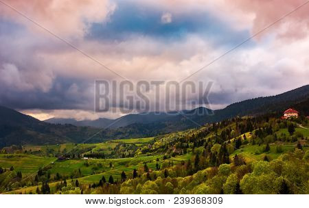Heavy Purple Clouds Over The Rural Countryside. Beautiful Landscape Of Carpathian Mountains In Sprin