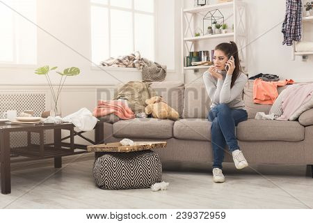 Desperate Helpless Woman Sitting On Sofa In Messy Living Room. And Talking On Mobile, Surrounded By