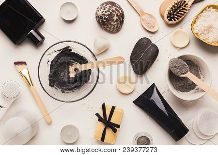 Preparing Cosmetic Black Mud Mask In Glass Bowl On White Background. Top View Of Facial Clay Emulsio