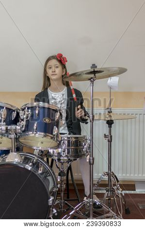 Young Caucasian Teenage Girl Plays The Drums. Girl Playing The Drum Set. Girl Learns To Play Drums I
