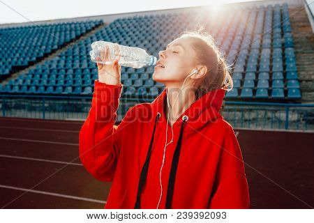 People, Lifestyle And Sport Concept. Sport Woman Athlet Overcame Long Distance, Drinks Water From Pl