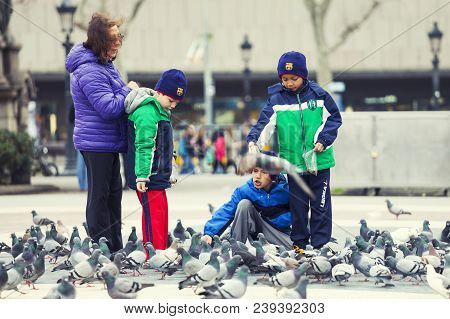 Barcelona, Spain. March 22, 2015: Little Children Playing With Pigeons In A Square In The Historic C