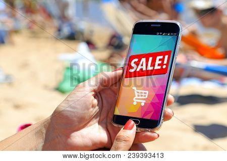 Girl On The Beach Holding A Smartphone A Sale Advertising On The Screen. Marketing, Discount, Intern