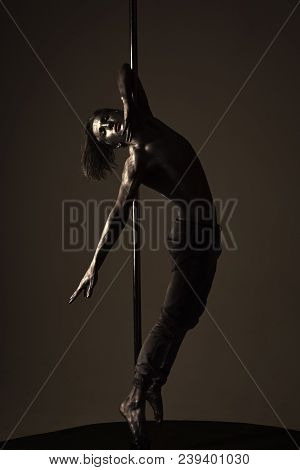 Performance Concept. Guy Hanging On Metallis Pole. Athlete, Sportsman Performing Pole Dancing Moves,