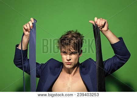 Macho Choose Necktie In Blue Jacket Shirtless On Green Background. Business Fashion, Style Concept.