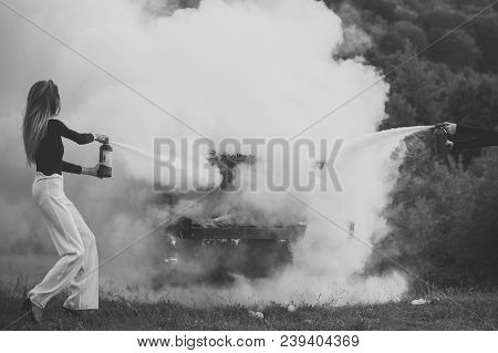 Fire And Smoke On Grunge Instrument. Firefighting Of Girl With Extinguisher. Sexy Woman With Long Ha