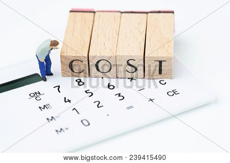 Business Costs And Expense Awareness, Miniature Figure, Man Carefully Looking At Wooden Stamp Block